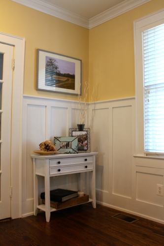 Completed wainscoting with a small, decorative console table to fill the empty space.